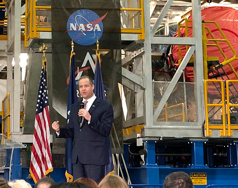 A man in a suit, standing under the NASA logo, in front of a machine set.