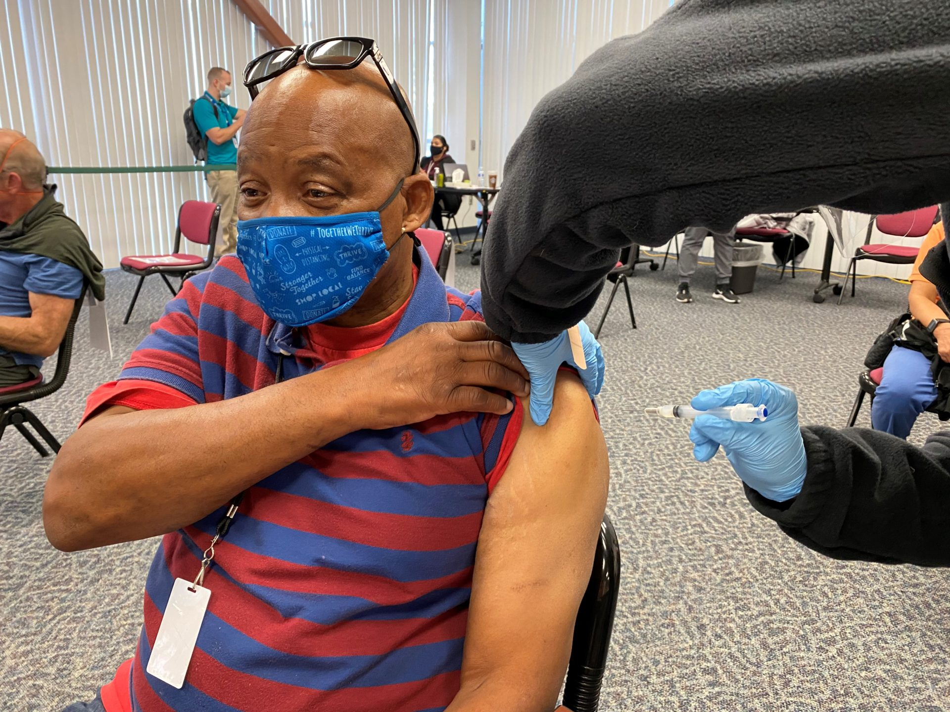 man wearing a mask gets a vaccination in his arm